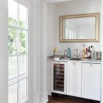 Small Nook For Bar In White Top With White Wooden Cabinet Under, Sink, A Mirror With Golden Frame Against The Wall