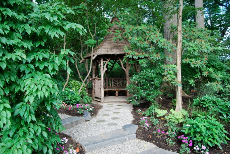 small wooden gazebo with wooden roof, wooden railes, poles and built in seating along the rails