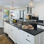 soapstone kitchen island hardwood floor carpet shelves books cabinets hanging lamps chairs painting