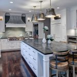 Soapstone Kitchen Island Wall Cabinets Hardwood Floor Transitional Kitchen Chairs Faucet Sink Ceiling Lights Shelves Books Hanging Lamps