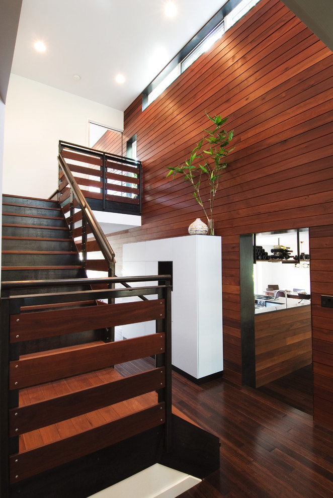 staircase with wood stairs, wood rails, wood covered wall