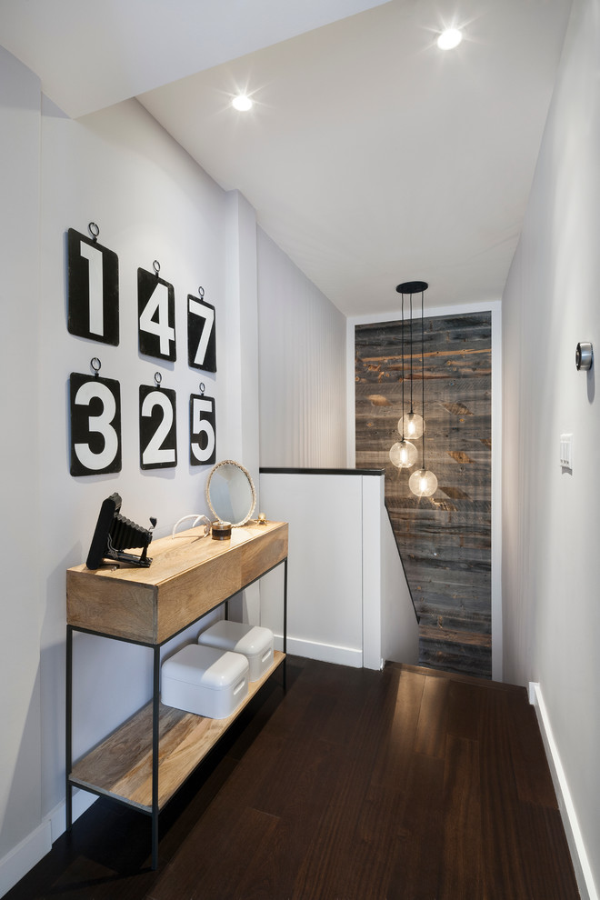 stairwell with wood wall dark wood floors simple barn console table with black iron accent