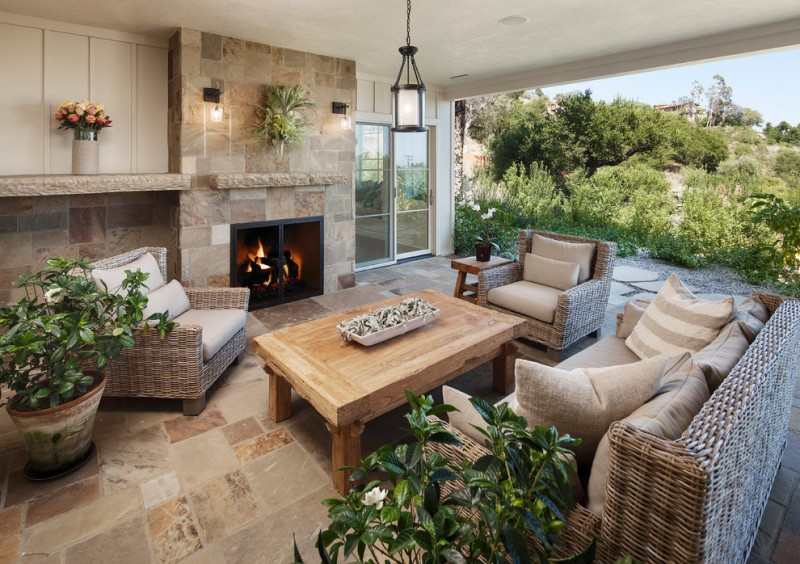 sunroom with brown flooring and fireplace, white pendant lamp, rattan sofa with beige brown cushion, wooden coffee table, sconces and plants on top of the fire place