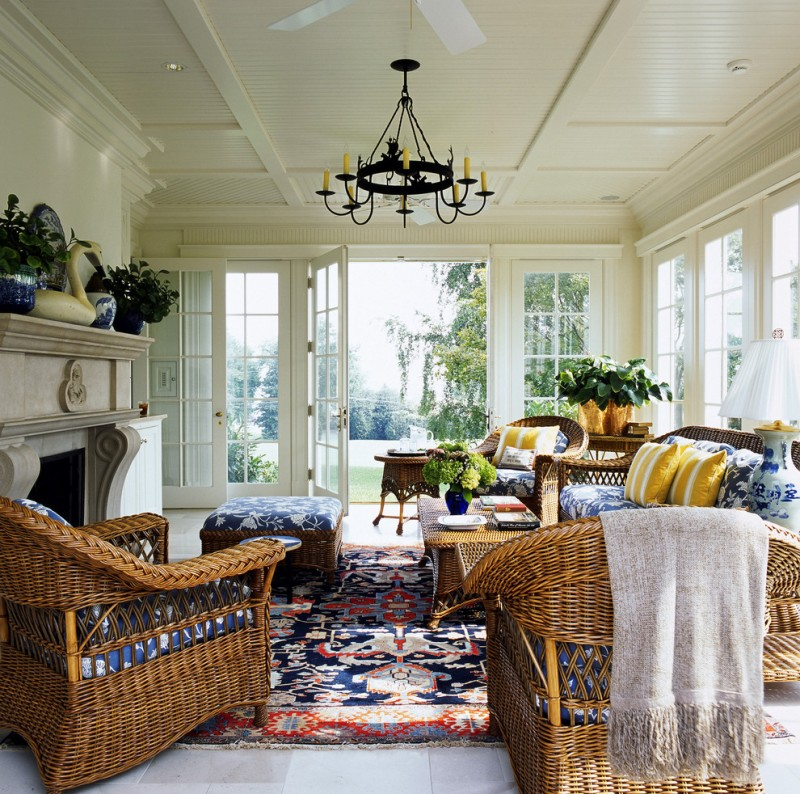 sunroom with white ceiling, wall, and flooring, rattan chair, sofa, and coffee table with mostly blue cushion and rug