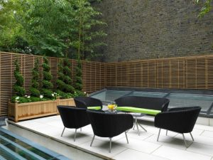 terrace color house chairs wood walls brick wall plants black greens brown small tables