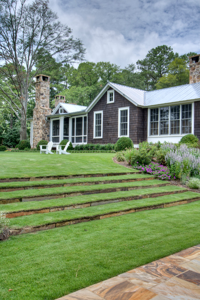 terrace color house green white brown exterior windows stones roof grass chairs farmhouse landscape