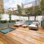 terrace color house wood floor seating table plants brick walls contemporary area