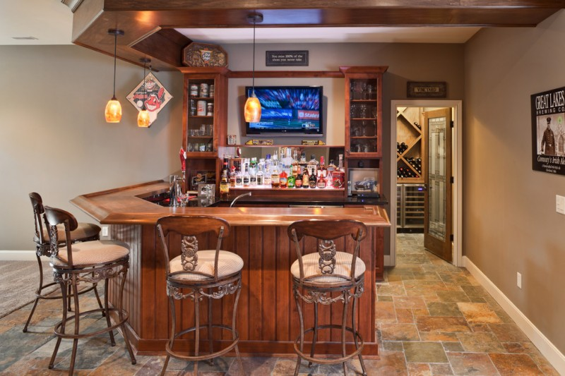 traditional bar with wooden bar table, wooden liquor cabinet, TV against the wall, yellow pendants, brown bar stool