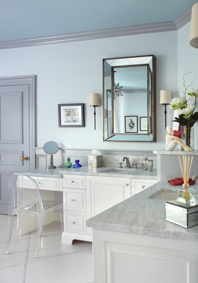 traditional bathroom with L shaped vanity with blue ish granite top, white cabinet under, white flooring, blue ceiling, medium sized mirror, clear plastic chair, sc