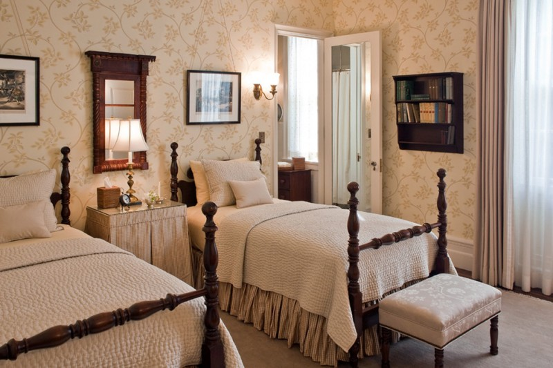 traditional bed room with twin bed in dark wooden bedding, cream bed cover, brown wallpaper, white ottoman, side table, mirror, shelves, sconces