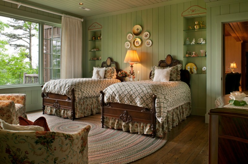 traditional bedroom with twin beds, brown wooden bedding, white cover, green wall, wooden flooring, rug, couch