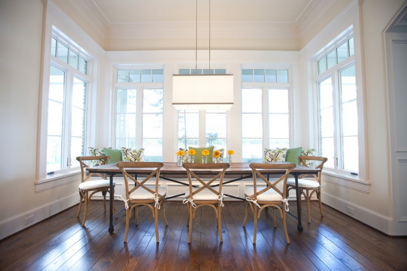 traditional dining room bright colour schemes hardwood floor big windows flowers chairs table pillows green brown hanging lamp
