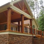 Traditional Front Porch Design With Stone Skirting Black Wrought Iron And Wooden Railing System