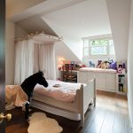Traditional Girls Wood Bed With White Bed Curtains Animal Stuffs Small White Area Mat Corner Study Table And Chair Darkwood Floors White Slanted Ceiling White Bench With Under Storage