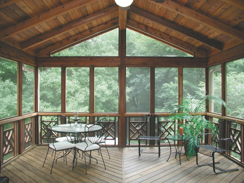 traditional porch with wooden ceiling, flooring, wooden window frame, with black iron chairs and tables with glass top, plants