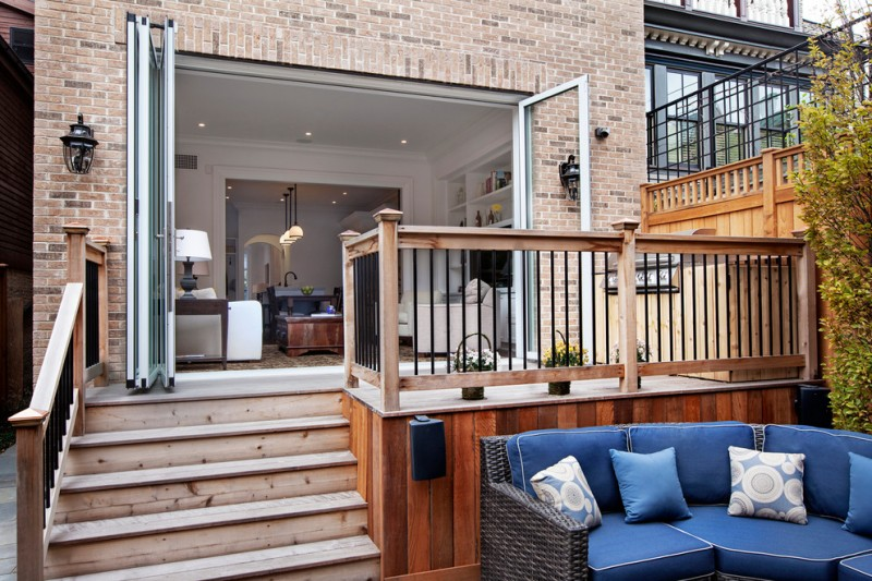 transitional patio with hardwood deck skirting white cedar deck floors black iron railings with wooden rail posts red bricks exterior walls black rattan patio couch with blue seaters