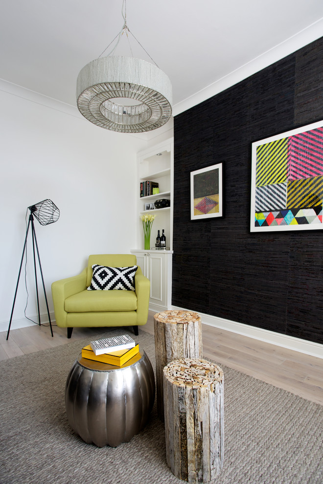 trendy living room with green arm chair a couple of tree trunk side chairs decorative side table with round top grey area rug black wall abstract painting pendant lamp tiny standing lamp