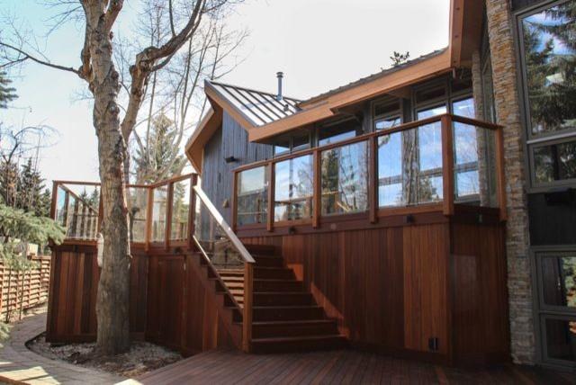 tropical deck with high level deck skirt made of dark wood transparent glass deck railing idea with dark wood frames dark wood exterior stairs with glass rail panel