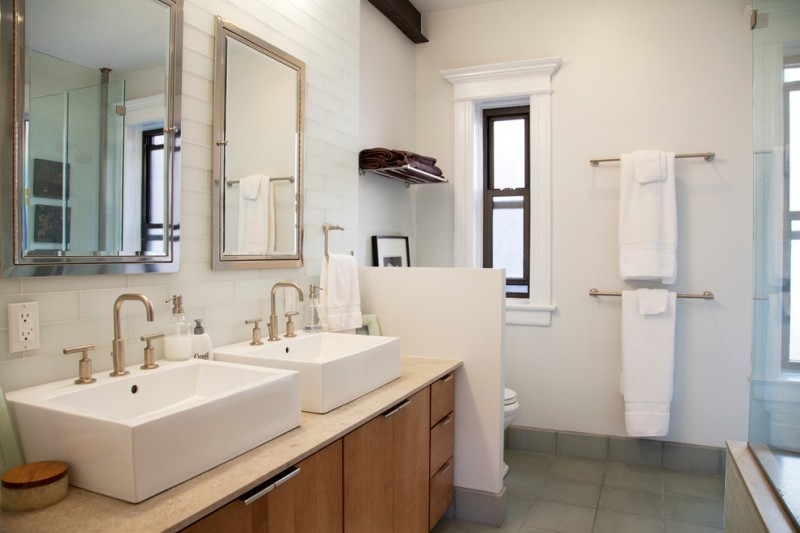 two white sinks on top of cream counter top with towel rack on the side of the mirror