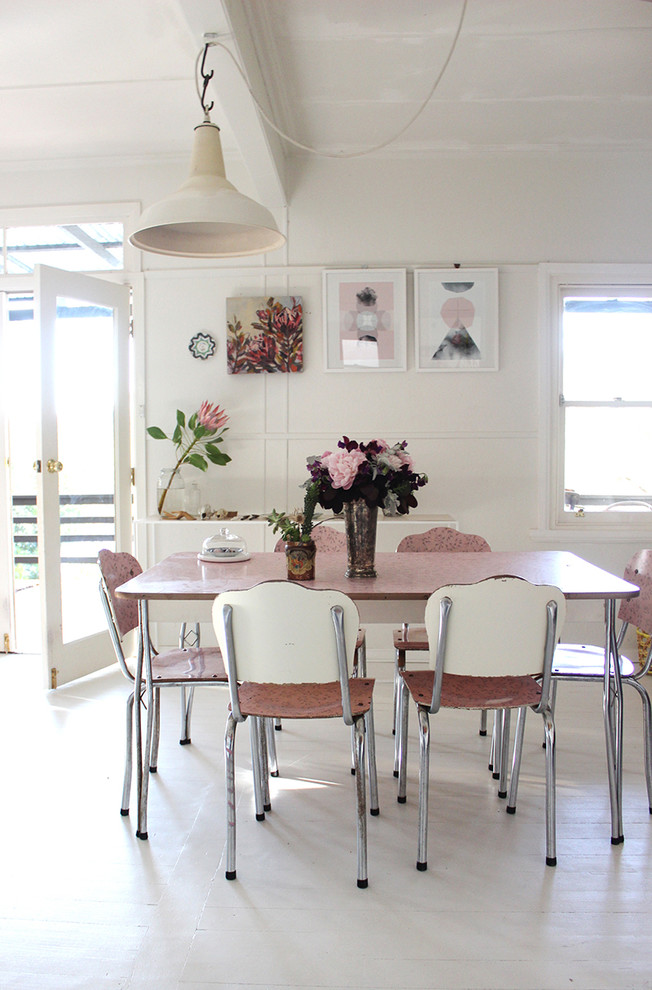 vintage dining furniture set in soft pink color clean white walls clean white floors several wall ornaments