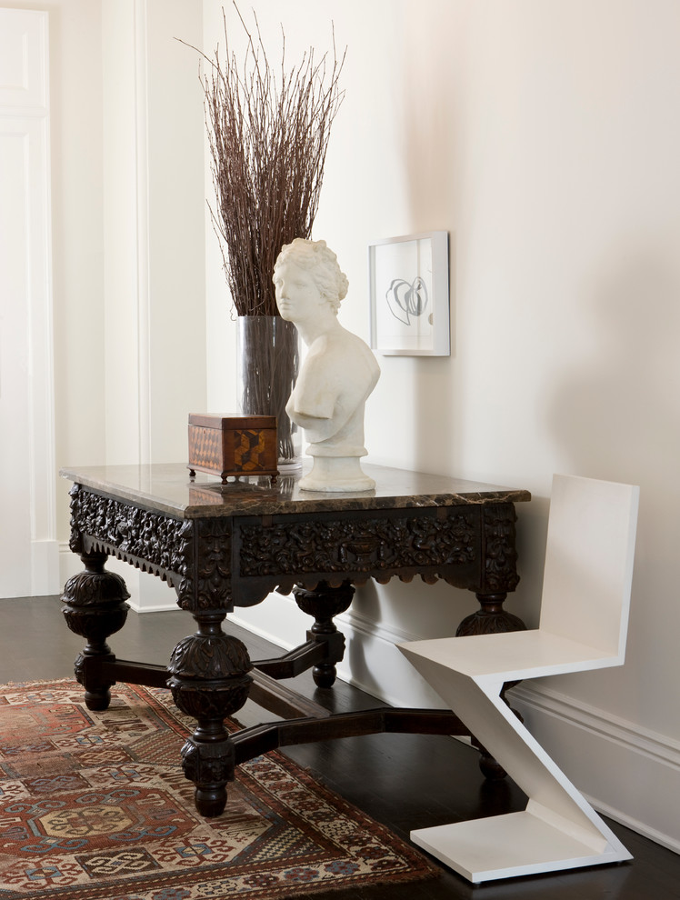 white classic Apollo statue dried grass ornament classic & antique wood entryway table in dark wood finishing white modern chair in white traditional area rug dark wood floors white walls