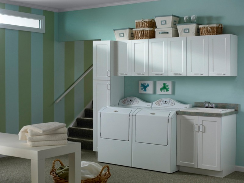 white contemporary laundry room with utility cabinets and coordinated rattan baskets
