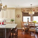 White Countertop Brown Cabinets Chairs Light Toned Wooden Floor Cream Walls White Ceiling Chandelier Lamps Raised Cabinets Window Drapes