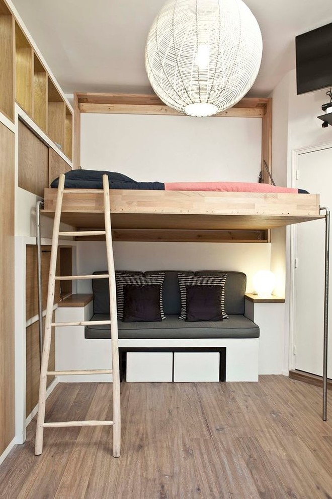 wood loft bed design with wood ladder wall mounted book shelves and sitting area at the bottom