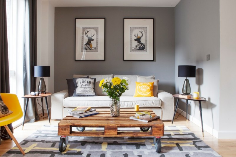 wooden coffee table with castors livingroom rug wall decoration gray wall yellow gray pillows yellow chair books glass vase