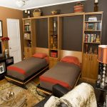 Wooden Unfolding Twin Bed With Grey Orange Cover On Brown Wooden Shelves