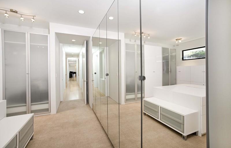 Floor to ceiling mirrored doors white cabinets cream carpet glass window deck wooden floor