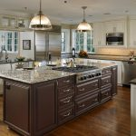 L Shaped Kitchen Idea With Dark Brown Kitchen Island With Granite Top And Raised Panels Cabinets Dark Toned Wood Floors Stainless Steel Appliances White Cabinets
