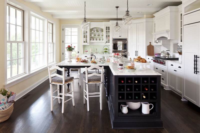 L shaped kitchen island with wine storage and chairs L shaped kitchen idea with white upper and lower cabinets stainless steel appliances dark toned wood floors