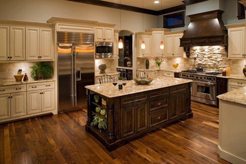 L shaped traditional kitchen design with white upper and lower cabinets stainless steel appliances white subway tiles backsplash textured bricks wall over stove granite top kitchen island with storage