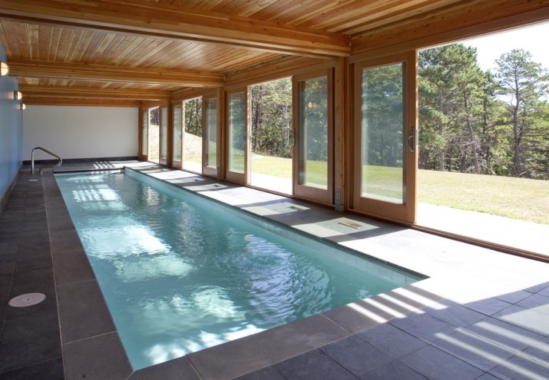 Mid Century pool idea with wood enclosure and sliding glass doors dark grey tiles floors simple rectangular pool white walls