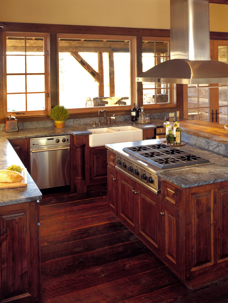 a small brown granite kitchen island with six stoves unter cooker hood