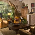 Arched Glass Doorway Stone Wall Wooden Cabinet Dark Wooden Coffee Table Leather Chairs Area Rug Stone Floor
