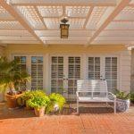 backyard patio covers brick pavers lantern lamp planting pots urn white bench double glass doors traditional design