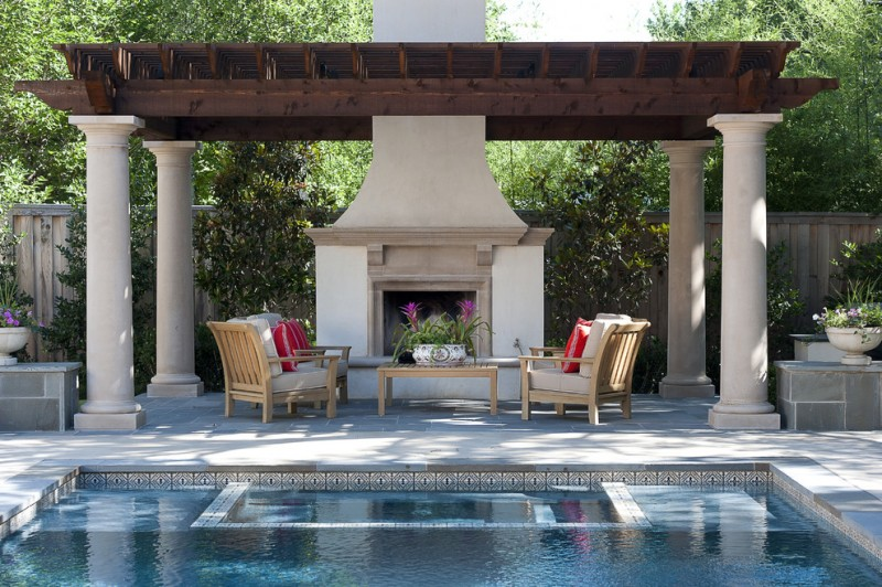 backyard patio covers set wooden chairs and table throw pillows fire feature flower centerpiece pool stone pillars traditional design