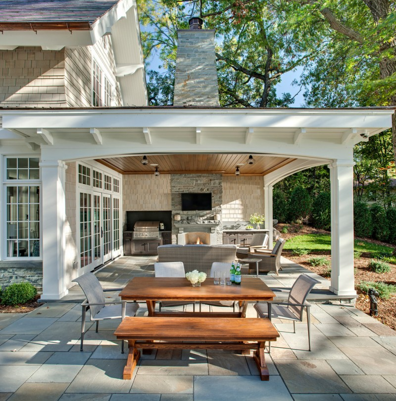 backyard patio covers set wooden table and bench tall back chairs sofa standard fireplace natural stone pavers wall mounted tv ceiling lights traditional design
