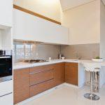 bar style kitchen table flat panel cabinets beige backsplash undermount sink stools oven concrete floors stove faucet contemporary design