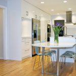bar style kitchen table flat panel cabinets undermount sink quartz countertops stainless steel appliances island chairs ceiling lights hardwood floors modern design