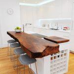 Bar Style Kitchen Table Island Flat Panel Cabinets Built In Shelves Double Bowl Sink White Backsplash Stools Wall Clock Hardwood Floors Eclectic Design