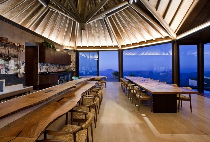 bar style kitchen table low back chairs stone tile backsplash cabinets kitchenette oversized windows medium tone hardwood floors tropical design