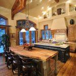 bar style kitchen table wood cabinets marble countertops island modern pendants undermount sink beige backsplash wall nooks stove hardwood floors rustic design