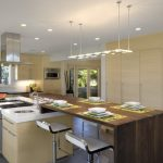 bar style kitchen table wood countertops flat panel cabinets sink ceiling lights stainless steel appliances stools island stove ceramic floors modern design