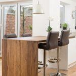 Bar Style Kitchen Table Wood Countertops Pub Stools Undermount Sink Cabinets White Pendants Folding Doors Wall Clock Hardwood Floors Contemporary Design