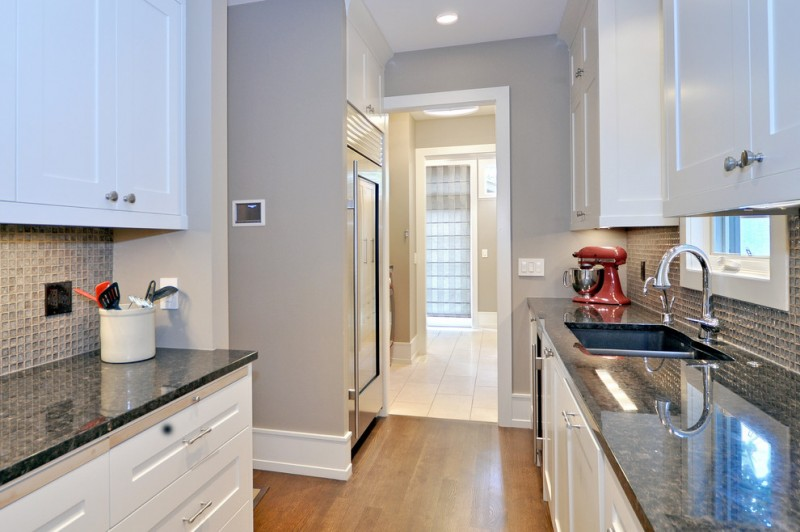 baseboard trim style hardwood floor countertops sink faucet window wall cabinets ceiling light transitional kitchen