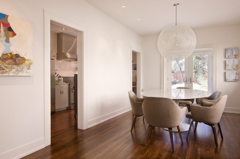 baseboard trim style hardwood floor painting chairs round top table glass door ceiling lights contemporary dining room
