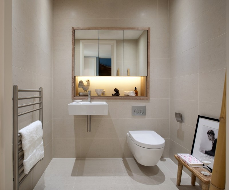basement bathroom floating white toilet floating white sink wood framed mirror small wood bench stainless steel towel hanger grey ceramic tiles floors and walls
